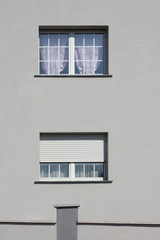 Rollladen als Sonnenschutz in grauer Fassade mit PVC Fenster