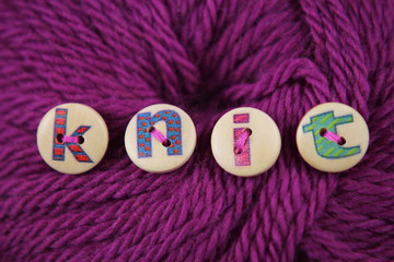 Lettered buttons spell the word knit sewn to a ball of wool