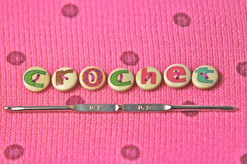 crochet spelled in lettered buttons on a pink wool background