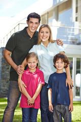 Portrait einer Familie vor Haus