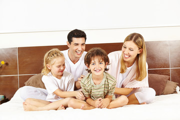 Glückliche Familie sitzt im Bett