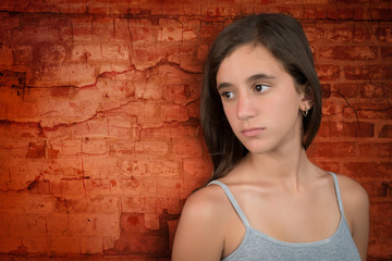 Sad teenage girl leaning on a bricks wall