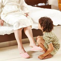 Kind hilft Seniorin zu Hause im Schlafzimmer