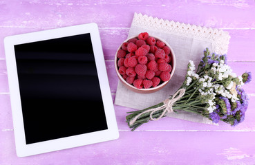 Tablet,, bowl of raspberries and bunch of wildflowers