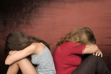 Teen daughter and mother sitting on the floor crying