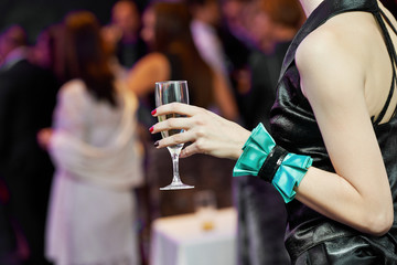 Guest hand and glass with wine at party