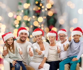 happy family in santa hats showing thumbs up