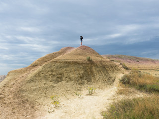 A tourist on the top of sandy hill in Badlands, South Dakota