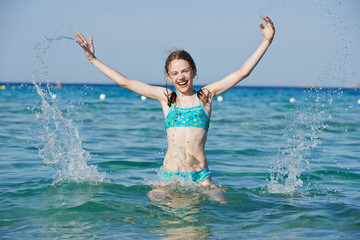 Exciting girl with sea water splashes