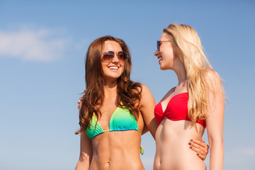 two smiling young women on beach