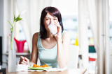 Cute brunette having breakfast and drinking milk, at home