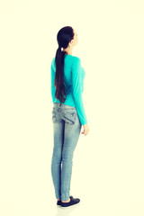 Young casual woman from behind looking up