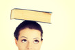 Attractive woman with book on head