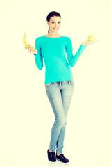 Young happy beautiful woman holding fresh fruits.