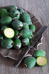Fresh feijoa (pineapple guava) on plate, selective focus