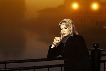 Young fashion woman against a night foggy landscape