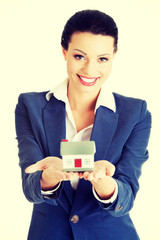 Beautiful businesswoman holding house model