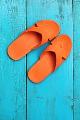 Orange flip flop sandals on blue wooden background