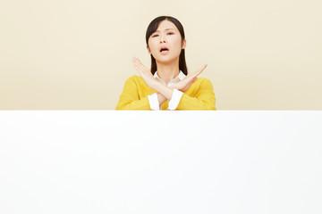 メッセージボードとバツ印する女性