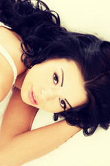 Happy sensual young woman lying in bed
