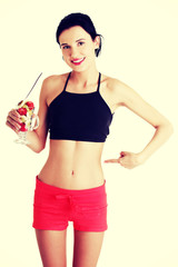 Pretty fit woman eating fruit salad