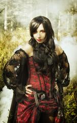 girl vampire in retro dress, in a black cloak, in the forest