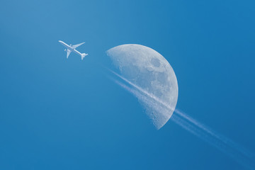 Airplane with Half Moon on a clear blue sky