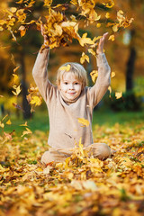 A boy throws up autumn leaves