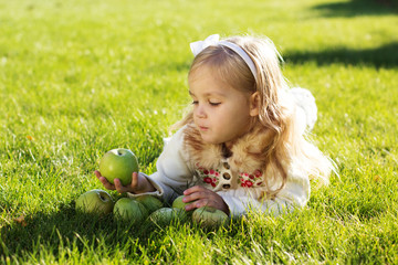 Child with green apples sitting on grass