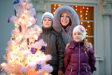 mother and two children near New Year tree against house