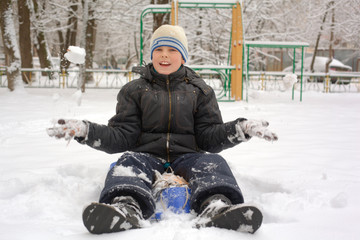 laughing boy sits in a snowdrift and plays snowballs