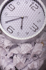 Close-up photo of a clock in refuse bin with other office rubbis