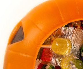 A plastic pumpkin filled with candy isolated on white background
