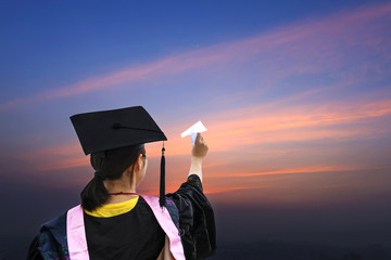 female graduate wearing a graduation gown, throwing airplane