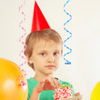 Young boy in holiday hat eating piece of birthday cake