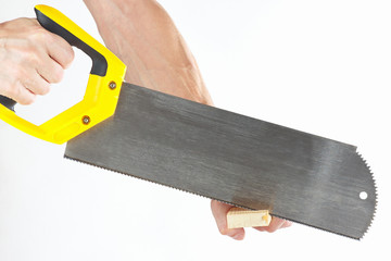 Hand  of a joiner sawing a wooden block with a hacksaw