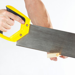 Hand of carpenter cutting a wooden block with a handsaw
