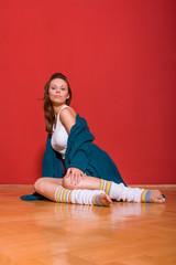 brunette sitting on the wooden floor
