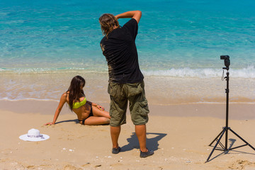 Photoshoot on the beach with beautiful bikini model