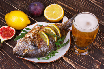 Whole grilled fish dorado served with lemon and figs;