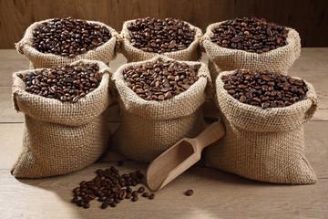 caffe chicchi in sacco su tavolo di legno