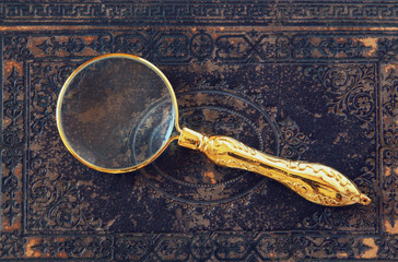 macro image of magnifying glass over antique black cover