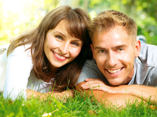 Happy Smiling Couple Together Relaxing on Green Grass