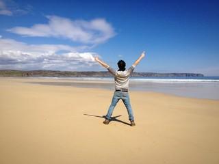 Young man exploring a remote beach in scotland