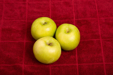 Three Granny Smith Apples on Red Towel