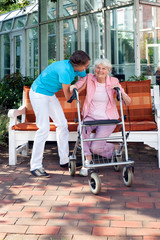 Senior woman being helped by a care assistant.