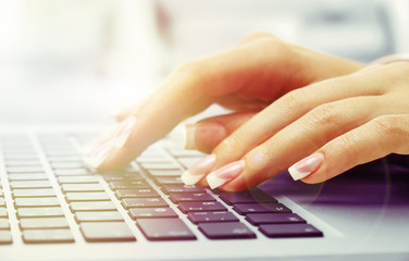 Female hands on laptop, close-up
