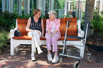 Two elderly friends chatting on a park bench.