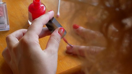 Woman Painting Nails with Red Color. Homemade Manicure.