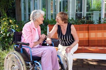 Two senior ladies chatting on a garden bench.